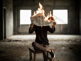 Mensch liest brennende Zeitung